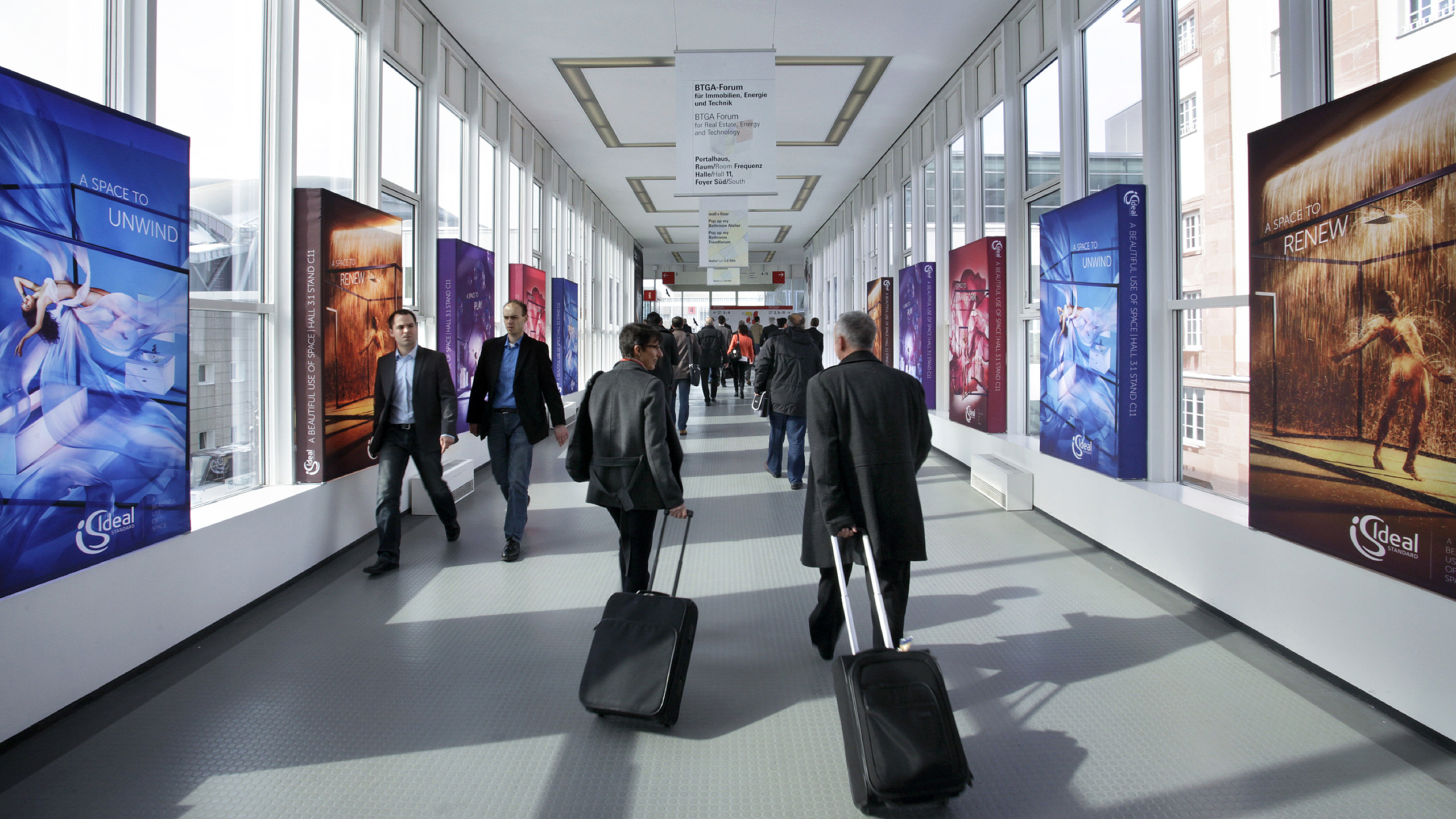 Trade fair visitors walk past advertising displays at Via Mobile